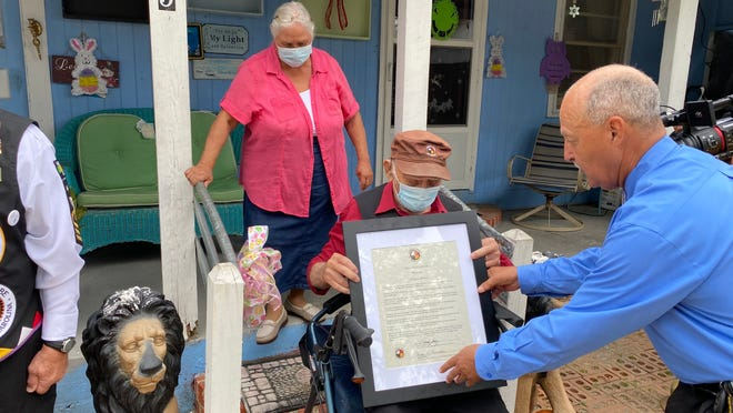 Gary Deese, with the Lumbee Warriors Association, presents Evert Locklear, a 102-year-old World War II veteran, with a proclamation in his honor March 27, 2021, at Locklear's home in Maxton.