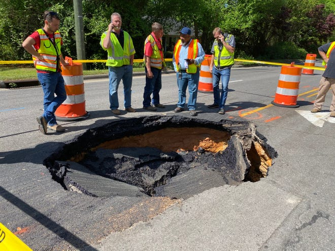 Crews stand around a 8-foot-wide sinkhole Tuesday on Morganton Road.