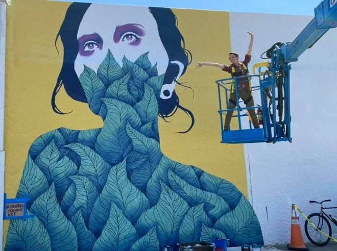 """Artist Heather Clements poses in the lift used to paint her mural, """"Essential Growth."""" Other murals are now in progress beside hers on the Welcome Wall for downtown Panama City."""