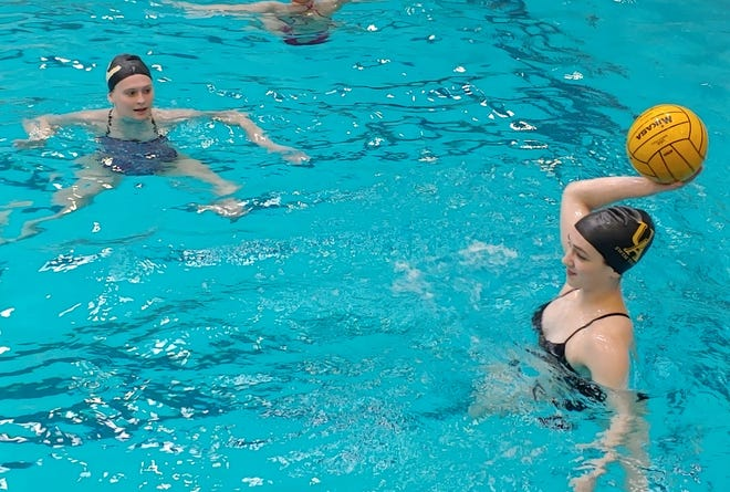 Upper Arlington girls water polo player Violet Houser tosses the ball during a practice drill April 12 as Caroline Ubert watches. The Golden Bears, defending state champions, are 12-0 entering the Milford Invitational on April 24.