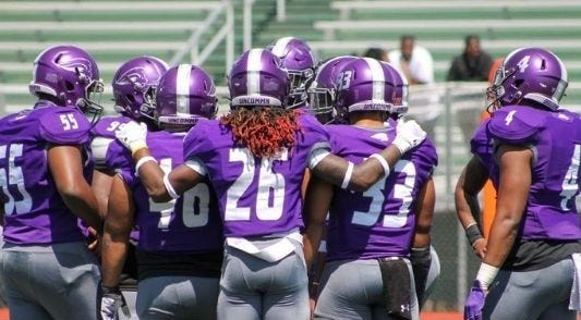Southwestern Assemblies of God football players huddle during Saturday's spring football finale against Oklahoma Panhandle State University. The Lions won, 27-24.