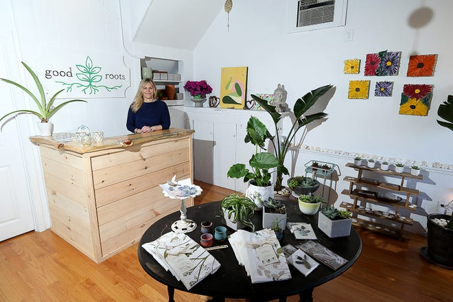 Jen Murphy stands behind the counter at her new shop, Good Roots, in North Scituate which sells plant arrangements, art, and household items.