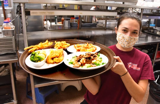 Alesha York takes an order out of the kitchen at Dixie Crossroads Seafood Restaurant in Titusville, a popular dining spot for people visiting the Space Coast for a launch.