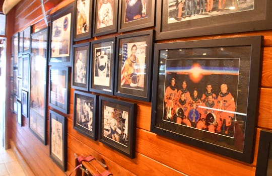 A wall in Dixie Crossroads Seafood Restaurant in Titusville is adorned with signed launch and astronaut photos.