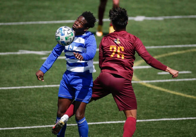 Drake senior forward Leroy Enzugusi, left, heads the ball upfield in the first half against Loyola of Chicago on Tuesday, April 13, 2021, at Drake Stadium in Des Moines.