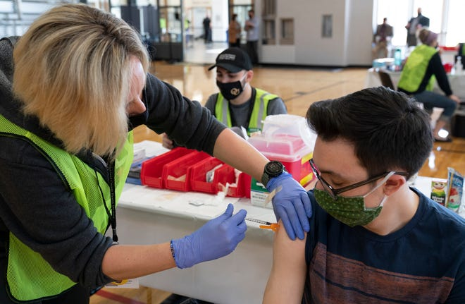 RN Danielle White with the Oakland County Health Department, left, administers the Pfizer Covid vaccine to third year pre-med student Gerard Knittel, 20, of Almont as Oakland University holds a Covid vaccine clinic at their Recreation Center for 18-24-year olds Tuesday, April 13, 2021.