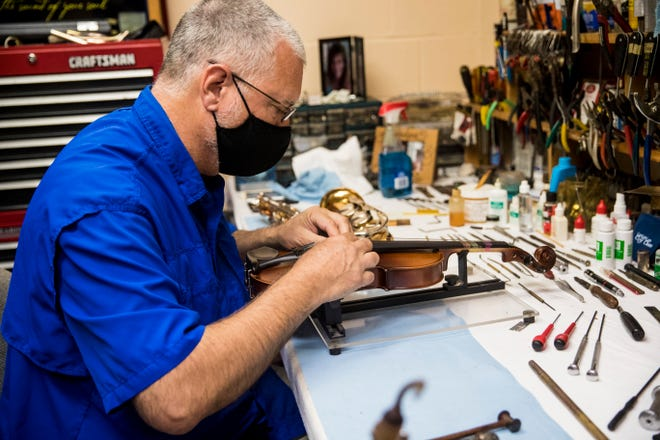 Michael Wenzlaff of First Note Music repairs a  violin in his shop at St. Michael Lutheran Church and School.