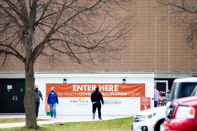 People walk in and out of the Prevea COVID-19 vaccine clinic held at the Kress Event Center in Green Bay Tuesday.