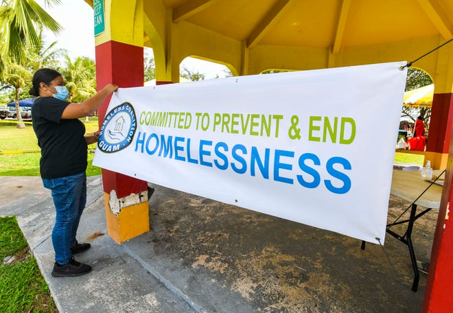 Salvation Army Support Specialist Julie Santos and fellow co-workers hang a banner to attract the attention of nearby homeless community members during an outreach conducted by the Guam Homeless Coalition at the Paseo de Susana Park in Hagåtña on Tuesday, April 13, 2021. Assistance and information on public welfare, housing, shelter, and other services were offered to individuals in attendance at the event. Refreshments and goody bags were also available to guests, as well as the opportunity to receive free COVID-19 vaccinations.