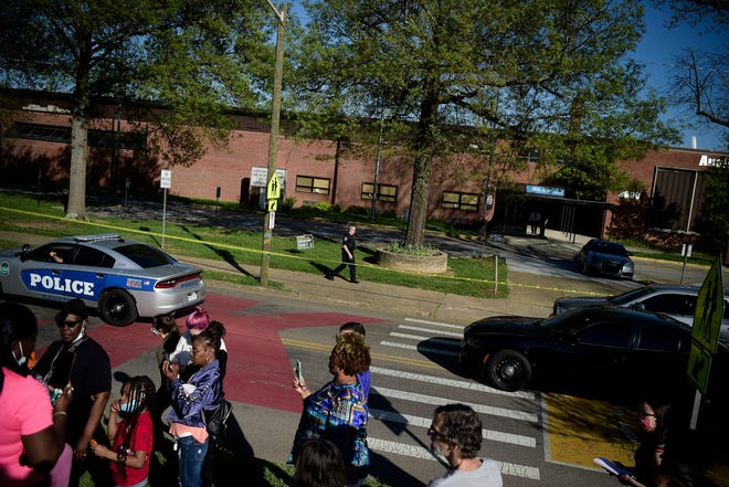 A Knoxville Police officer walks in front of the school as community members gather at the scene of a shooting at Austin-East High School in Knoxville, Tenn. on Monday, April 12, 2021.