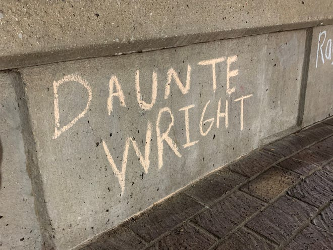 Daunte Wright's name was written in chalk at Jefferson Square Park Monday. Wright, a 20-year old Black man, was killed by a police officer during a traffic stop Sunday in Minnesota.