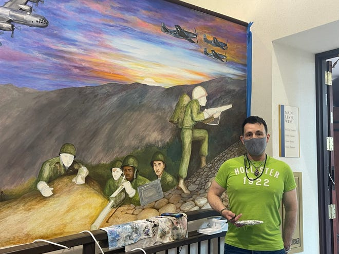 With music playing from his phone and plenty of painting tools on hand, William Obenour has been spending his days in the Marion County Building painting a mural for the Korean War exhibit.