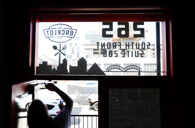The finishing touches are applied to the entrance of Backlot Sandwich Shop off Front Street downtown Tuesday, April 13, 2021.