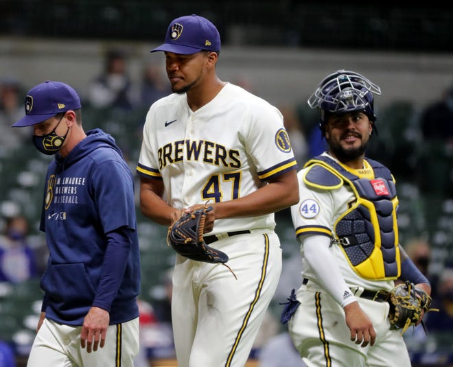 Brewers relief pitcher Angel Perdomo heads to the dugout Monday night after it was discovered he wasn't on the lineup card for the game against  the Cubs.