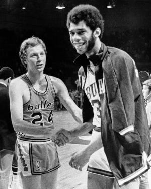In this April 30, 1971, file photo, Milwaukee Bucks' Lew Alcindor, who later was renamed Kareem Abdul Jabbar, smiles as he receives congratulations from Baltimore Bullets' Jack Marin (24) after winning the NBA championship in Milwaukee. The Bucks' first season wasn't all that dazzling at 27-55 in 1968-69. But then they drafted Alcindor with the No. 1 pick. In 1970-71, the Bucks captured an NBA title by sweeping the Baltimore Bullets.
