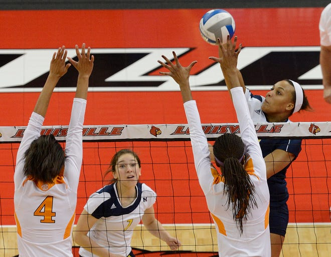 Michigan's Molly Toon, right, attempts to score over the defense of Tennessee's Olivia Okoro, right, and Tiffany Baker during a first round match in the NCAA Division 1 women's college volleyball tournament, Thursday, Nov. 29, 2012, in Louisville, Ky.