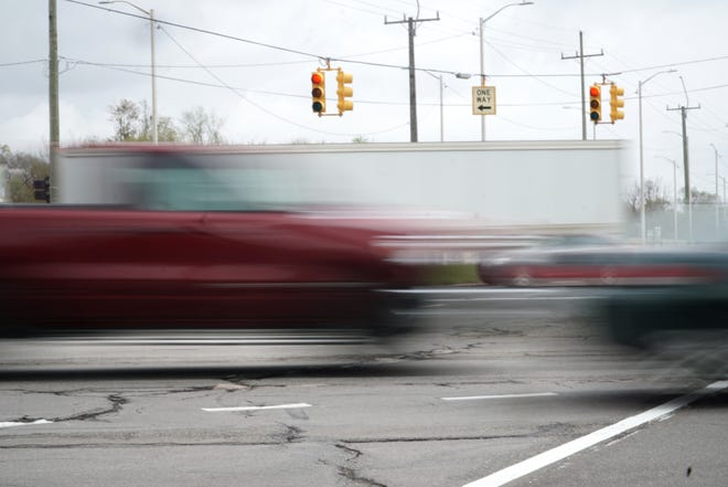 Traffic blurs past the intersection of Telegraph Road and Grand River Avenue on April 12, 2021.