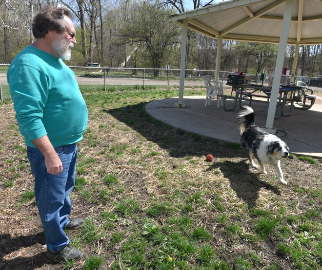 Larry Fields hangs out with his Australian shepherd Buddy on April 13, 2021 at the Wayne County Dog Park.