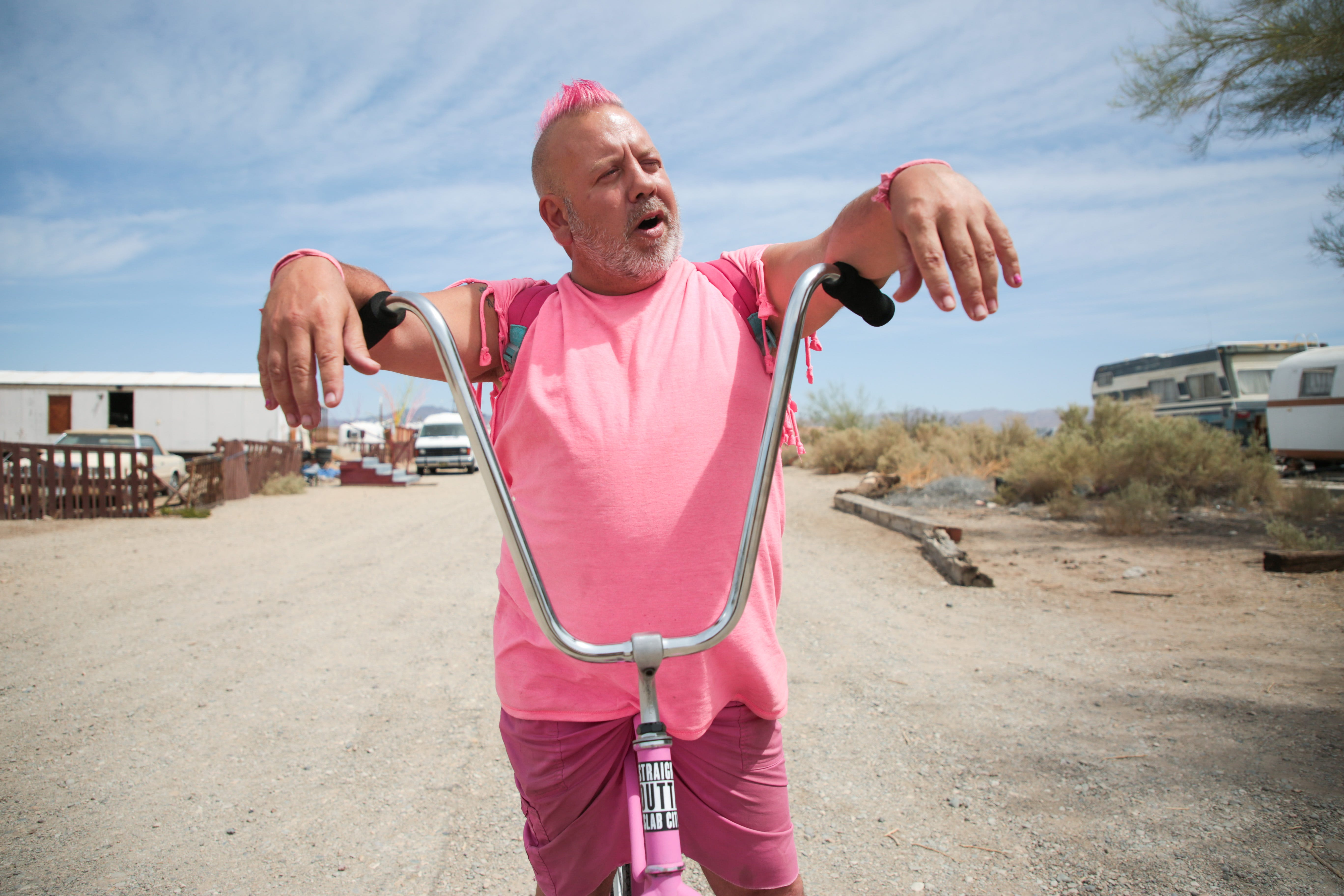 Pink Gorilla stops to chat on his bike in Slab City, Calif., on Monday, April 5, 2021. He said he believes the COVID-19 pandemic is a hoax and will not get the vaccine.