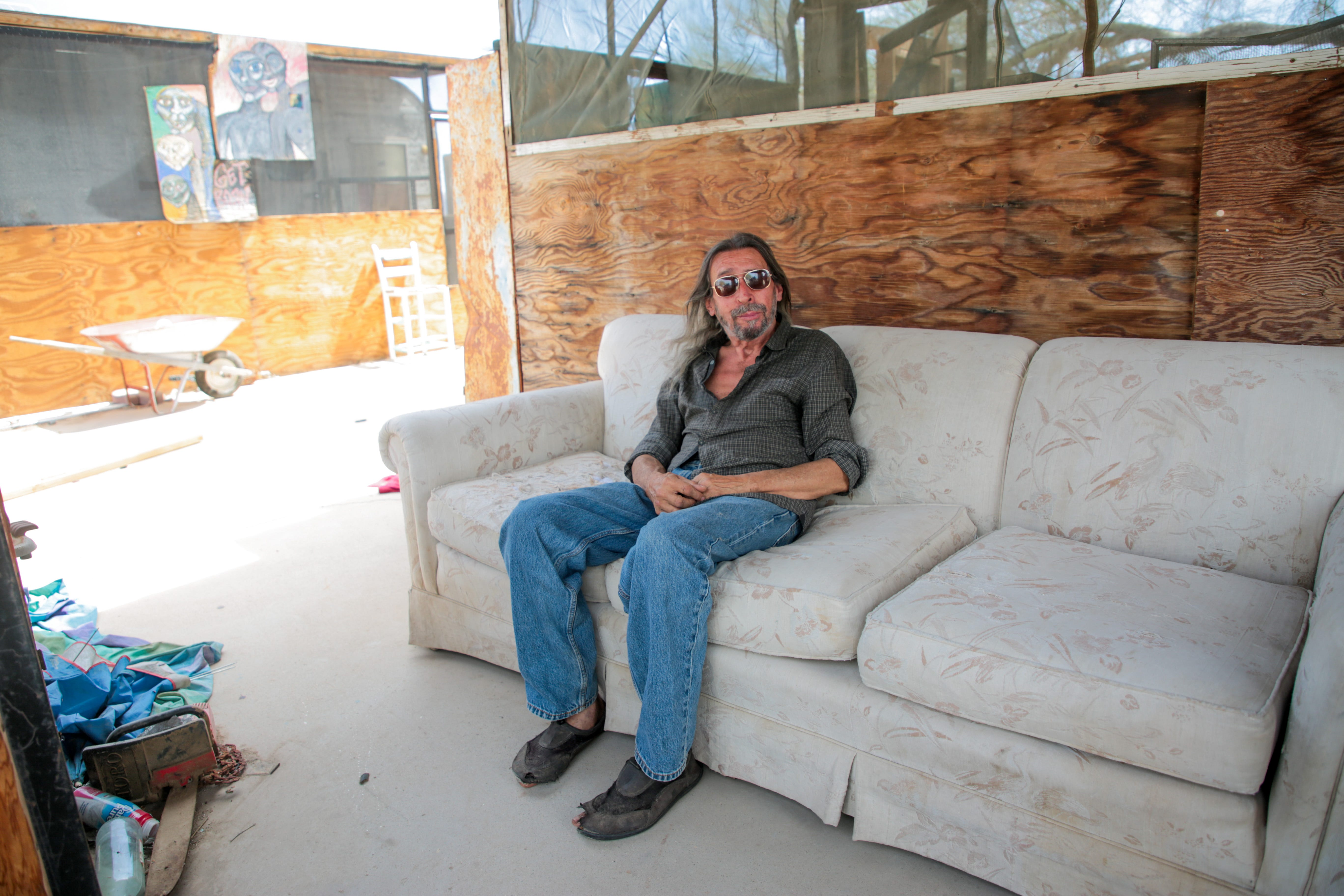 Carlos Gonzales sits on a couch near The Range in Slab City, Calif., on Monday, April 5, 2021. Gonzales received both doses of his COVID-19 vaccine.