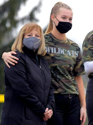 Dallastown's Macy Schaefer hugs her mother Debra Schaefer during Military Night before a game at Dallastown Monday, April 12, 2021. They were honoring Clark McWilliams, a family member who served in the Air Force and was a prisoner of war. Dallastown players wore special camouflage jersey's bearing the name of the service member they honored during the team's game against New Oxford. Bill Kalina photo