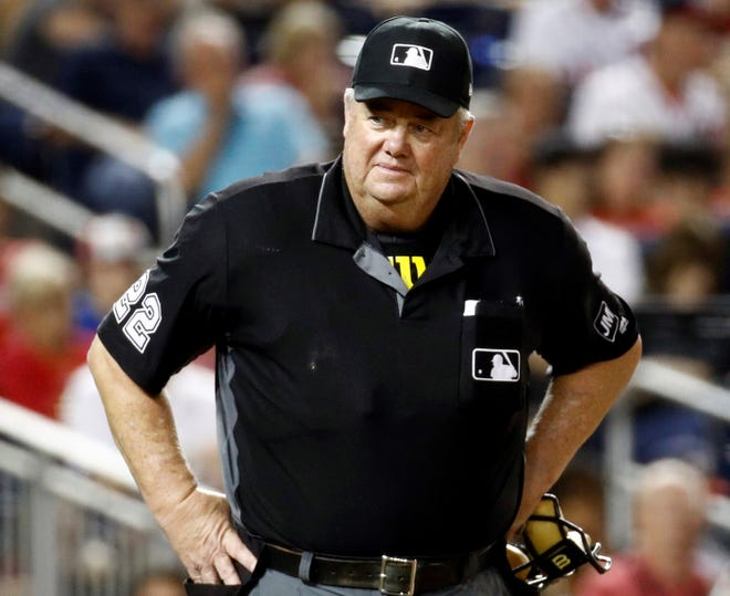 FILE - In this Sept. 27, 2019, file photo, umpire Joe West stands on the field during a baseball game between the Cleveland Indians and the Washington Nationals in Washington. Major league umpire West was awarded $500,000 in damages plus interest dating to July 8 in a defamation suit against former All-Star catcher Paul Lo Duca. (AP Photo/Patrick Semansky, File)