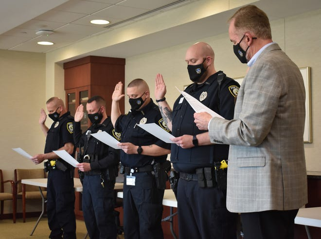 Craig Kinyon (right), president and CEO of Reid Health, swears in Reid Health Police Department Officers Scott Jackson (from left), Cory Jenkins, Billy Terhaar and Scott Roberts on Monday, April 12, 2020.