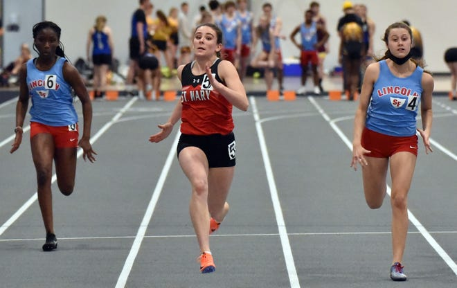 St. Mary sprinter Ella Heinitz runs in a 60m preliminary event at the Lancer Invitational on March 14 against Sioux Falls Lincoln's Jennifer Noutsougan (left) and Elizabeth Jerstad.
