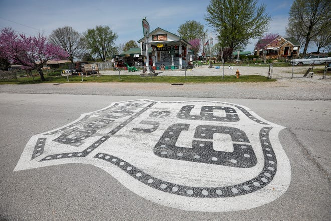 A large Route 66 shield has been painted on the road in front of Gay Parita Sinclair along Route 66 near Halltown, Mo.