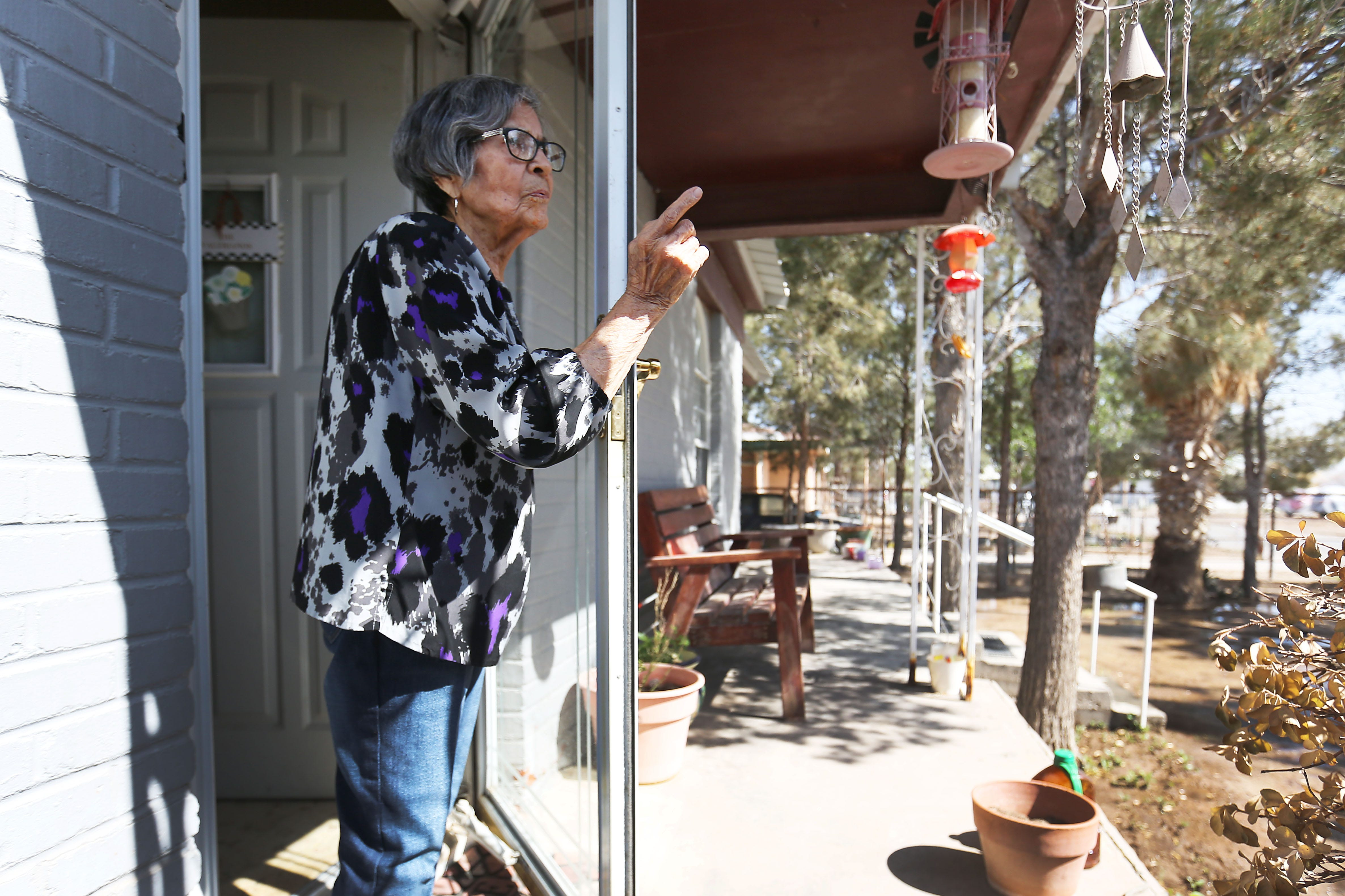 Maria Baeza Valeriano stands on her front porch talking about her neighborhood Friday, April 9, 2021, in Pecos. Maria lives right across the street from what used to be a housing area for oil field workers. It is now being used as a migrant shelter for unaccompanied minors.