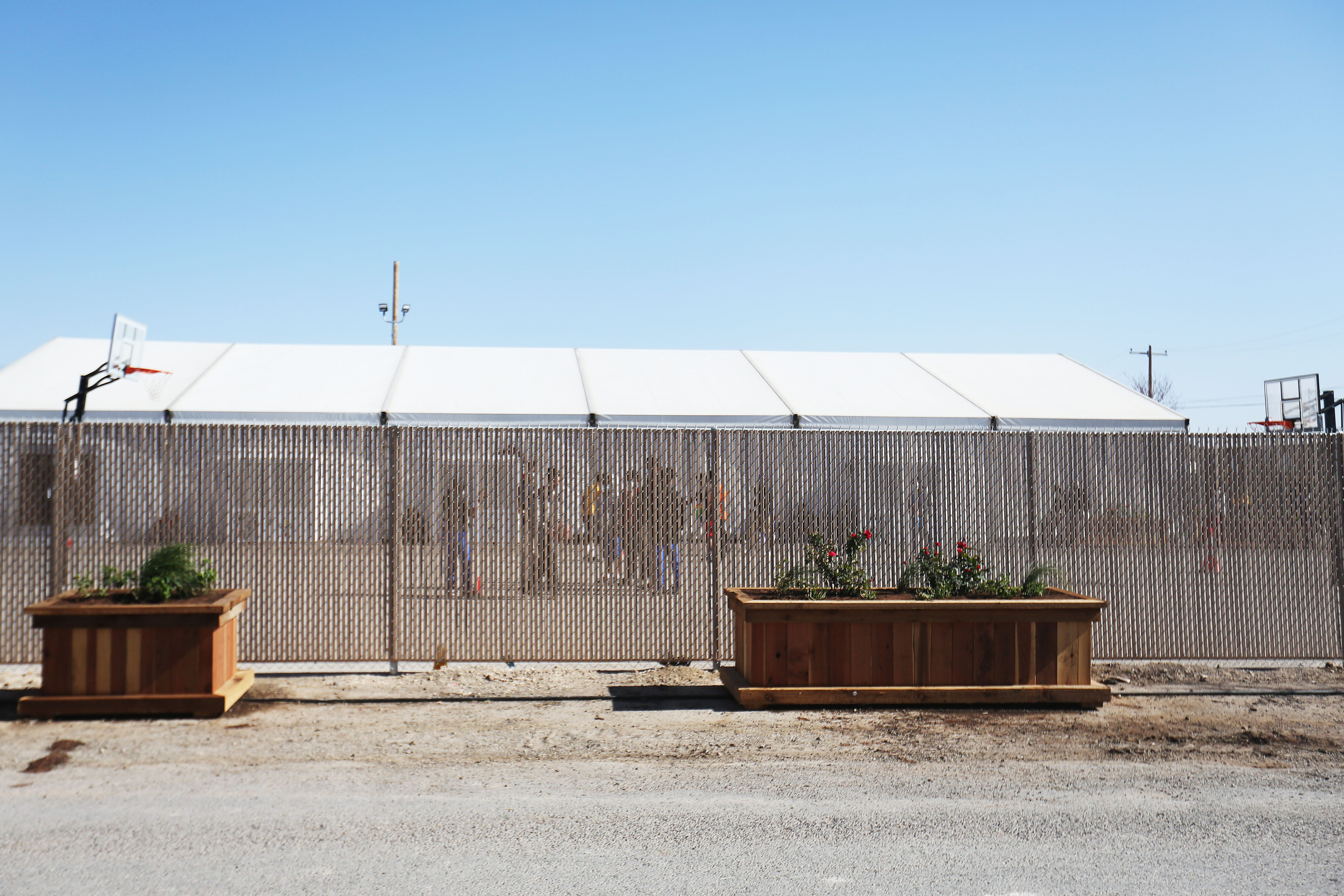 Migrant children play outside at a shelter for unaccompanied minors Friday, April 9, 2021, in Pecos. The property is owned by Target Hospitality. It was formally being used by oil field workers for lodging while at a job worksite. It is now housing migrant children.