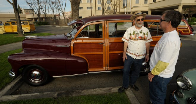 """Woodies owners Wayne Yada, left, of Visalia and Daniel Dews, of Los Angeles, catch up in front of Daniel's 1948 Chevy Fleetmaster Woodie Friday afternoon outside the Visalia Marriott as they gather for the 8th annual """"Woodies in the Valley,"""" an all Woodies car show held March 8 on the front lawn at Redwood High School, 1001 W. Main St., Visalia."""
