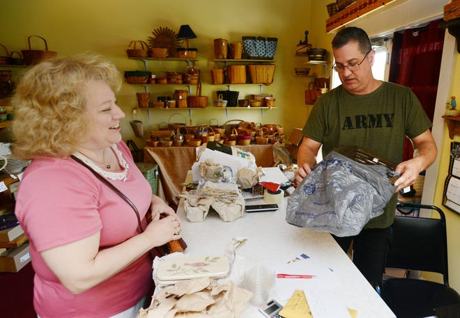 In this 2015 file photo, Geoff Snyder, owner of The Basket Guy in Dresden, wraps a Longaberger basket for a customer. Muskingum County tourism officials hope that as more people receive COVID-19 vaccines popularity will increase for high exposure-risk indoor activities like shopping.