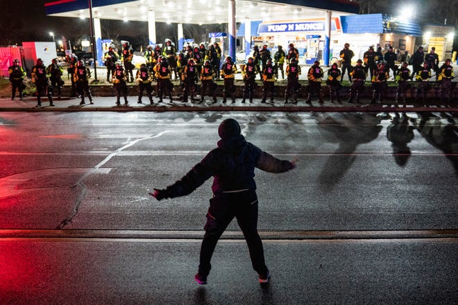 A demonstrator heckles authorities who advanced into a gas station after issuing orders for crowds to disperse during a protest against the police shooting of Daunte Wright, late Monday, April 12, 2021, in Brooklyn Center, Minn.