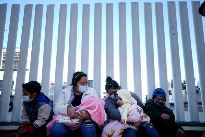 El Salvador and Honduras nationals seeking asylum in the United States sit outside the El Chaparral border crossing on February 19, 2021 in Tijuana, Mexico.