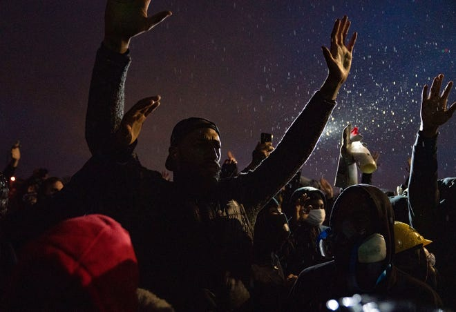 Protesters raise their hands in front of the Brooklyn Police Department a day after Daunte Wright was killed by police in Brooklyn Center, Minn. on April 12, 2021.