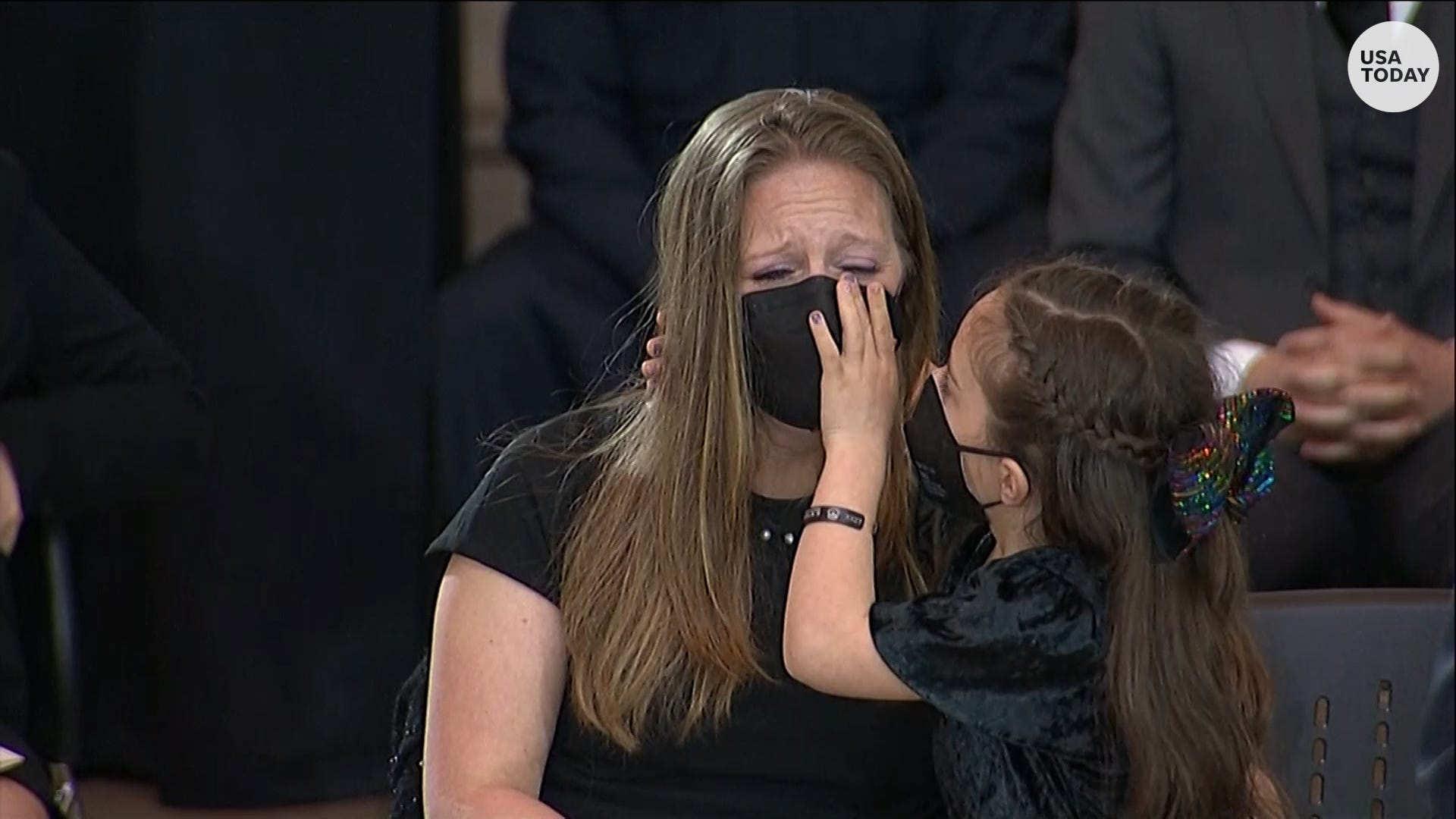 Daughter of fallen Capitol officer kisses mother as she becomes emotional