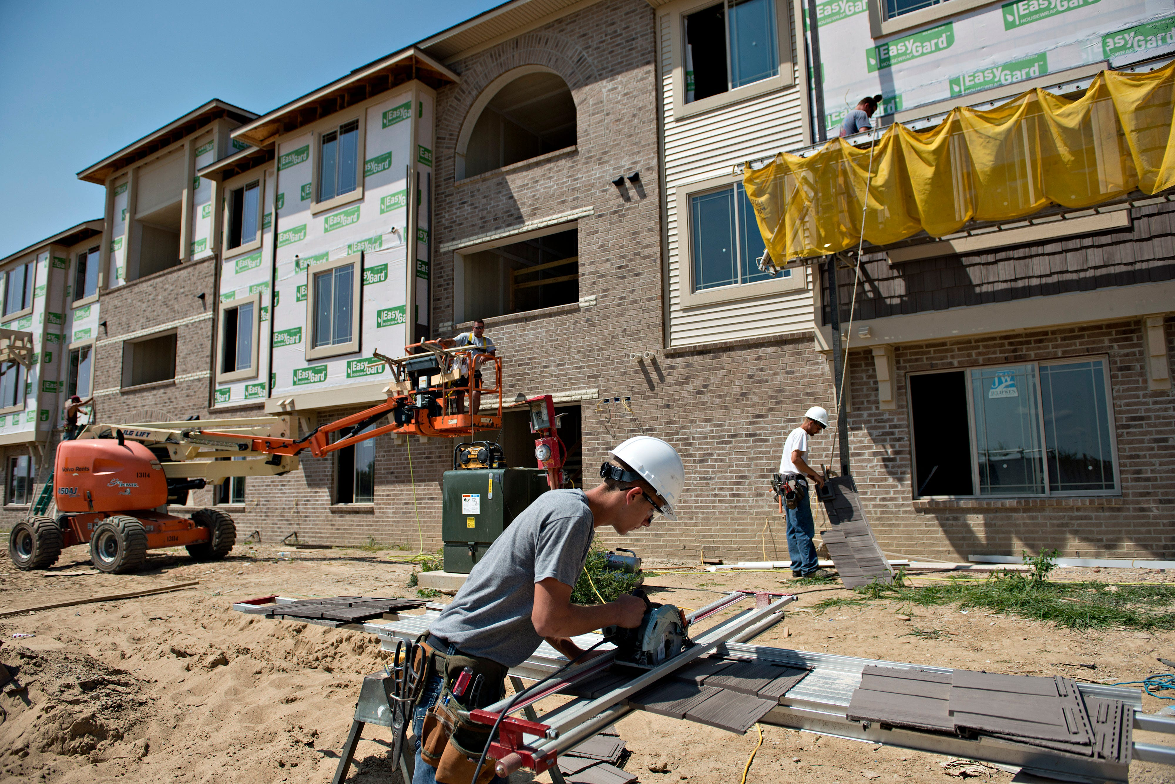 Joe Genusa cuts a piece of siding outside an apartment building under construction in Peoria, Illinois, on Friday, Aug. 16, 2013.