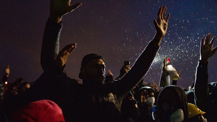 Protesters raise their hands in front of the Brooklyn Center Police Department on Monday, a day after Daunte Wright was fatally shot by police in Brooklyn Center, Minnesota.