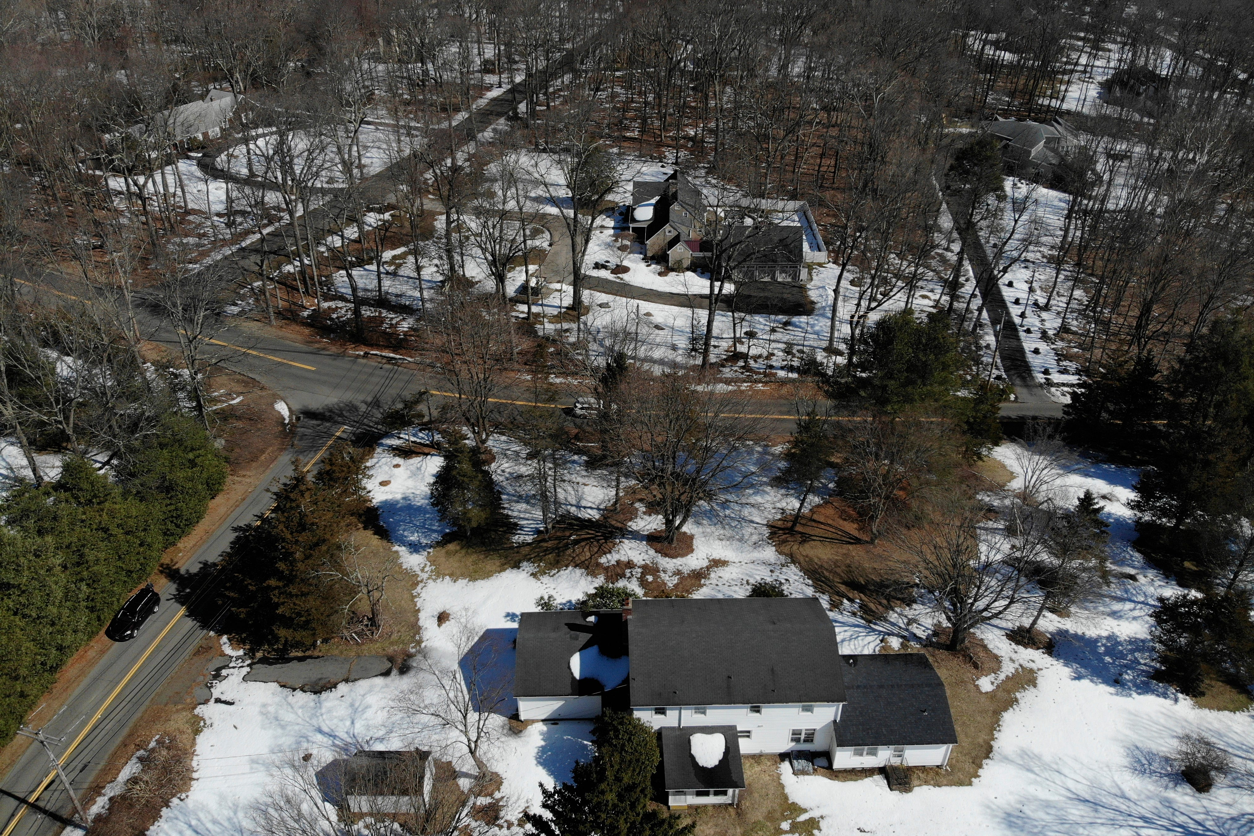 A five-bedroom house, bottom, is seen in Woodbridge, Conn., Wednesday, March 3, 2021.