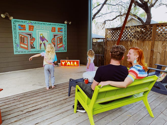 The Bullard family of Austin use an existing gray wall on their house to project movies and to play games outdoors. They've hosted some socially distanced screenings with friends during the pandemic, too.