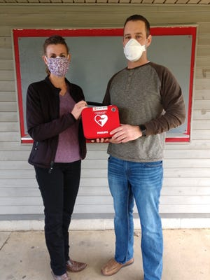 Deb Lewis, nurse practitioner in the Pomerene Family Care office in Loudonville, presents an AED to Eric Stitzlein, Loudonville Youth Association president, recently. Pomrerene Hospital in Millersburg donated the AED to the Loudonville Youth Association.