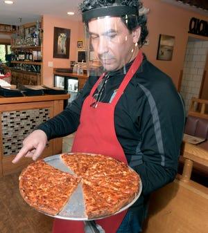 Ο Paul Bolanos, φορώντας μια ασπίδα προσώπου για να σταματήσει η μετάδοση του COVID, διανέμει δωρεάν φέτες πίτσας σε μέγεθος ορεκτικών στο Royal II.