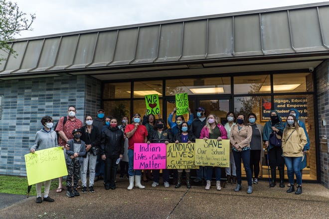 Pointe-aux-Chenes parents, residents and other supporters stand outside in the rain and wind Tuesday evening waiting for the School Board meeting to start.