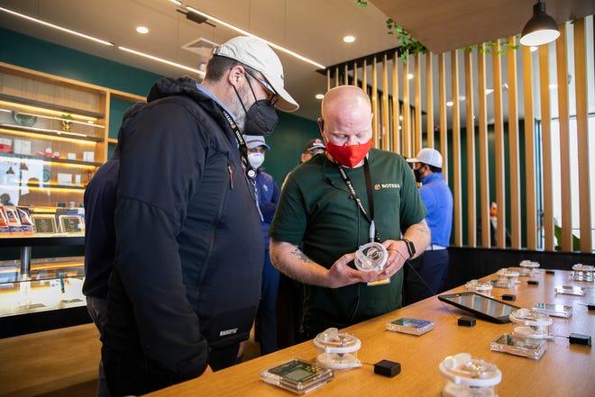 Botera budtender Brian Loomis gives Botera COO Matthew Hoffman, of Maynard, the full personal shopping experience at the new recreational marijuana dispensary at 747 Centre St. Brockton on Wednesday, April 14, 2021.
