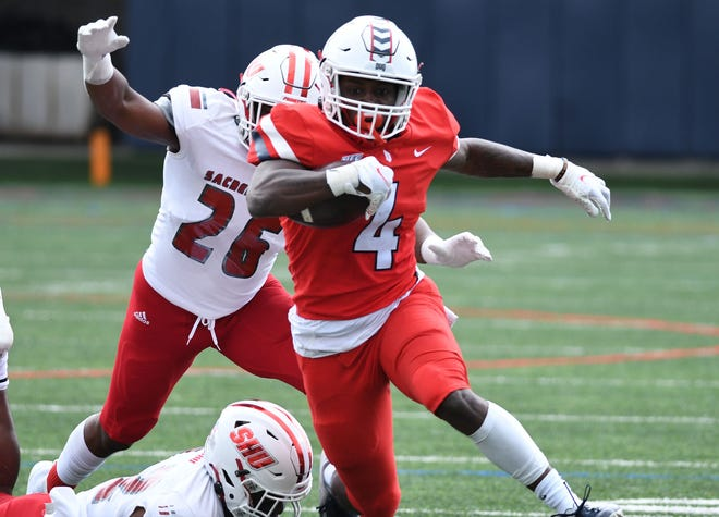 Cathedral Prep graduate Billy Lucas, center, gains yardage for Duquesne on Sunday, April 11, 2021, in the NEC championship game agaisnt Sacred Heart at Rooney Field in Pittsburgh. Sacred Heart won 34-27 in overtime.