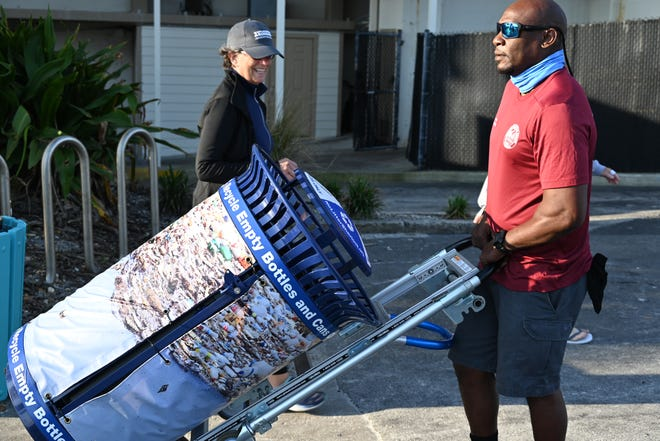 """A resident smiles as Atlantic Beach public works employee James Payton wheels a new high-tech recycling bin into place at Beaches Town Center. Atlantic and Neptune beaches received the bins from Keep America Beautiful, which also is kicking off its national """"No No )*#@r (Litter) Sherlock"""" campaign in the two cities."""