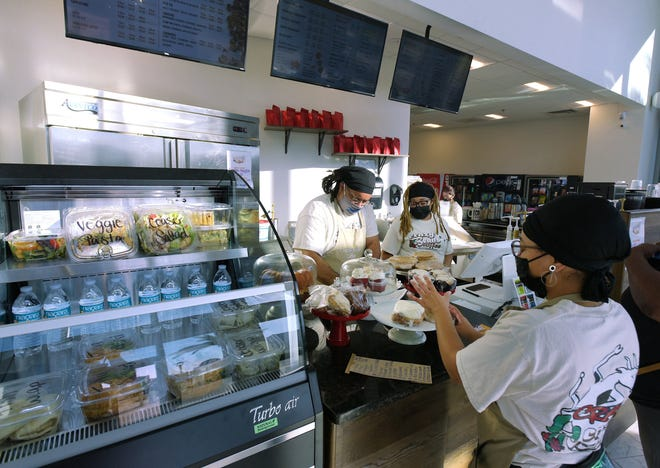 Assistant Manager Don Ashton, left, and cashier Dianthe Ashton work behind the counter at the new Crazy Beans Coffee, located on the ground floor of the Jacksonville Regional Transportation Center in LaVilla. Jourdan Ferguson places freshly-made pastries on a display at the counter.