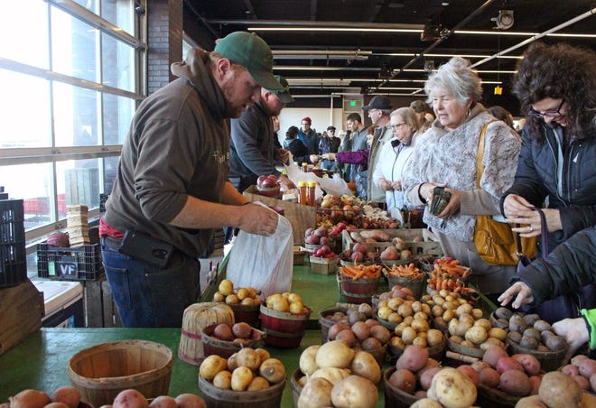 Produce is sold during an indoor farmers market at Holland Civic Center Place in January 2019.