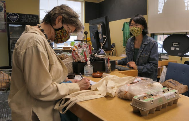 Ann Zimmerman of Saline County buys eggs, vegetables and bread from Maya Kathrineberg at Prairieland Market in Salina.